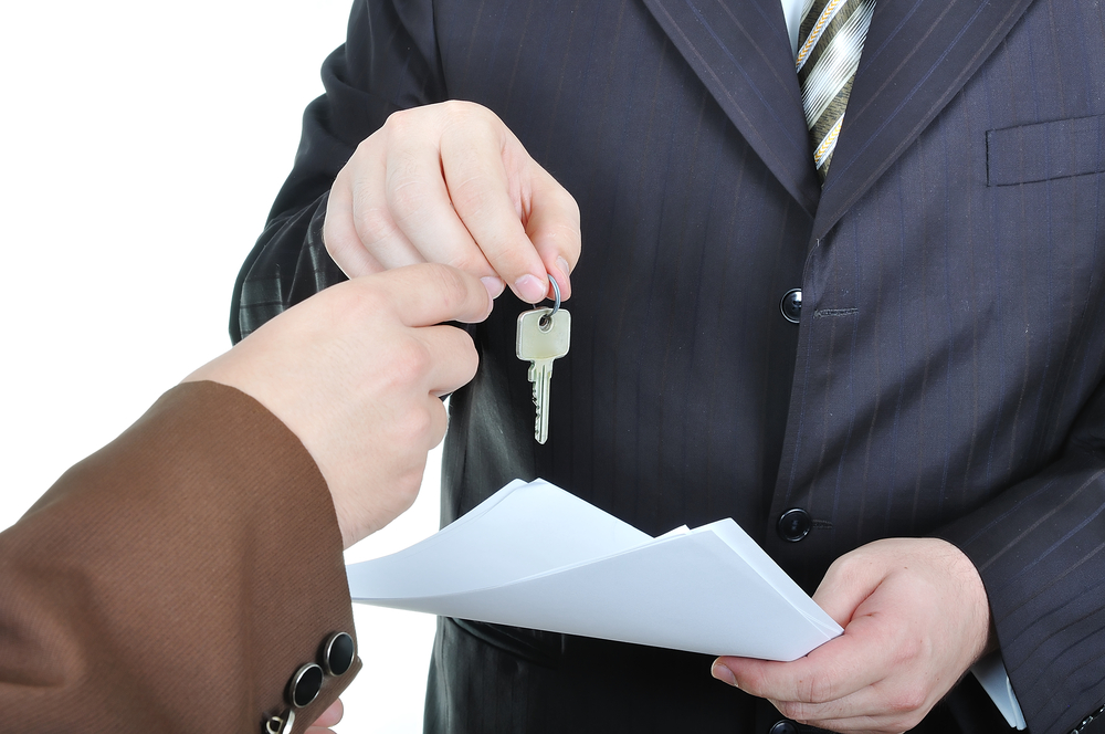 Two businessmen hands and the key, paper agreement