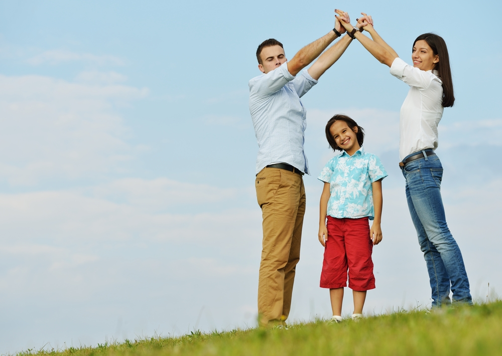 Young family on green summer grass meadow building dream new home